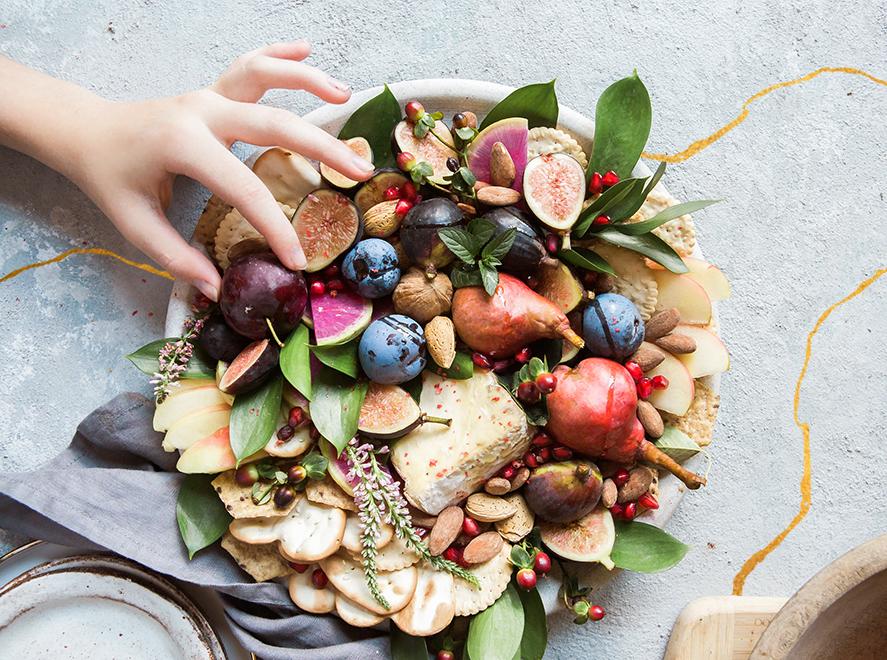 Un plateau de fromage avec des fruits, des figues et des poires, posé sur une table en béton avec une ligne doréé de Kintsugi