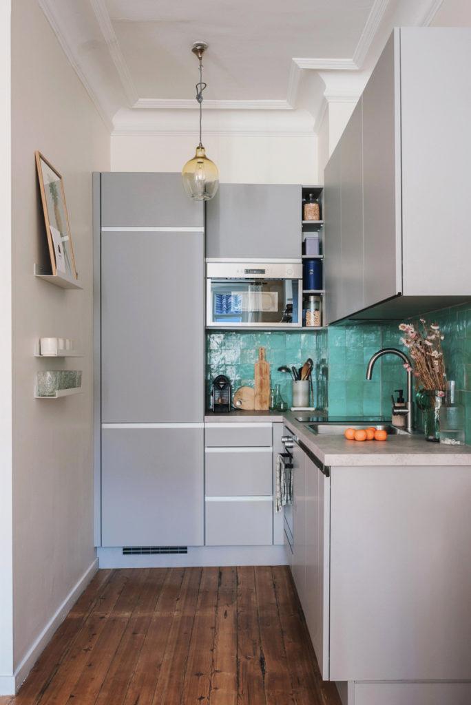 Cuisine minimaliste avec meubles hauts et bas gris clair et crédence en zelliges turquoises.