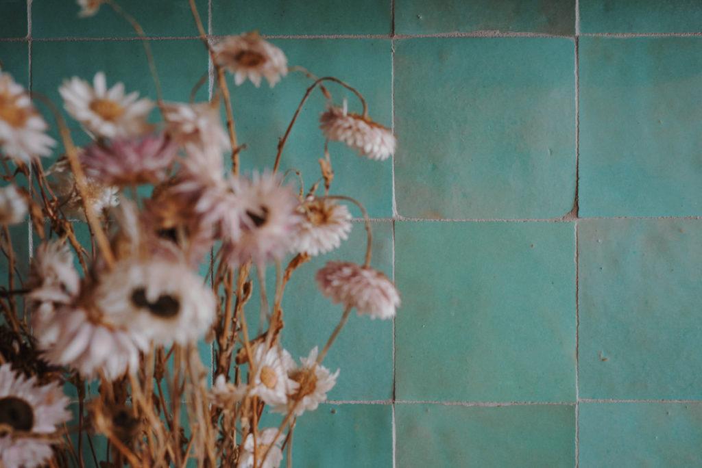 Un bouquet de fleurs séchées devant la crédence en zelliges.