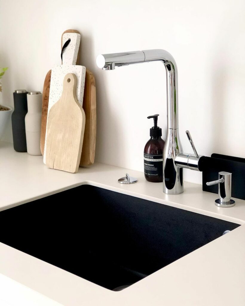 Cuisine minimalise : zoom sur les équipements avec un évier sous plans de travail et un robinet en métal gris