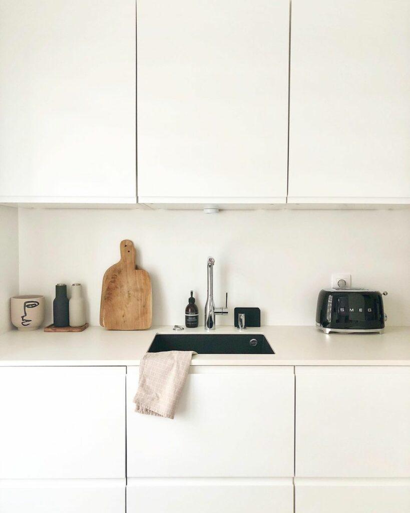 Façade de cuisine minimaliste, des portes et un plan de travail blanc.