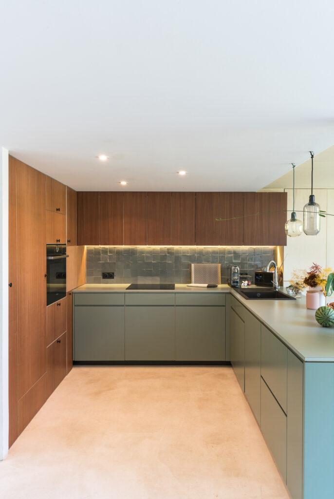 Cuisine aux couleurs et matières naturelles : la cuisine ouverte est organisée des meubles bas vert, des meubles hauts en bois foncé et des équipements noirs. Décoration : des plantes vertes et des fleurs séchées.