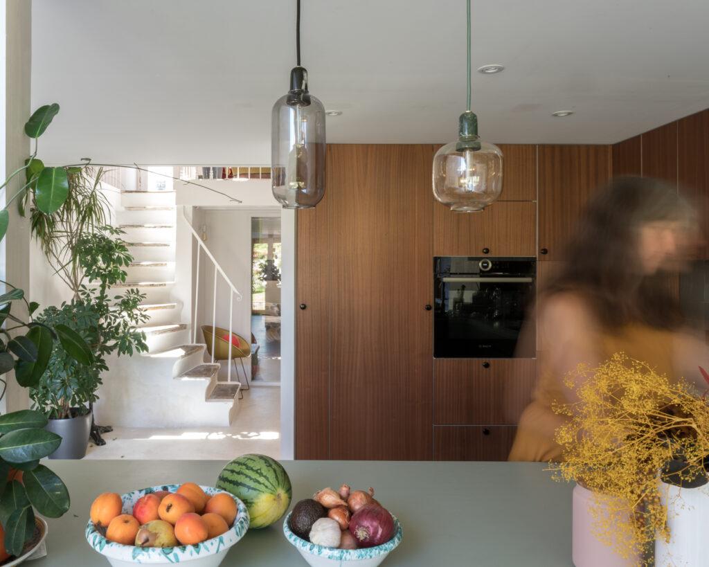 Cuisine aux couleurs et matières naturelles : zoom sur le plan de travail vert et les meubles en bois. Décoration : des coupelles de fruits en céramique et des plantes.