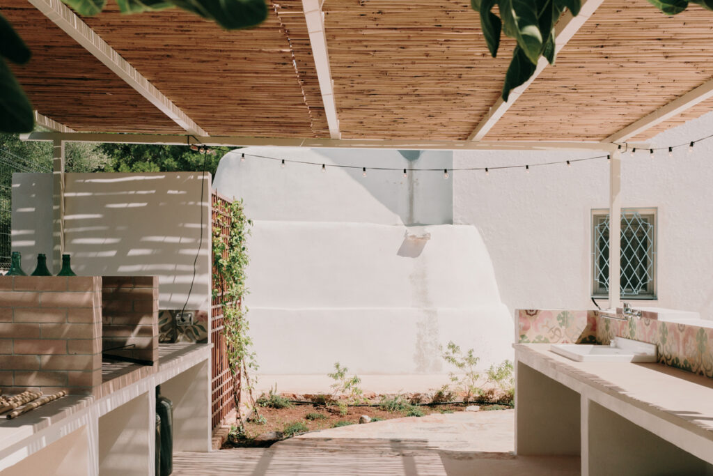 Cuisine bucolique : une cuisine extérieure sous une pergola pour profiter des beaux jours. A droite un évier en céramique, à gauche un barbecue en briques.
