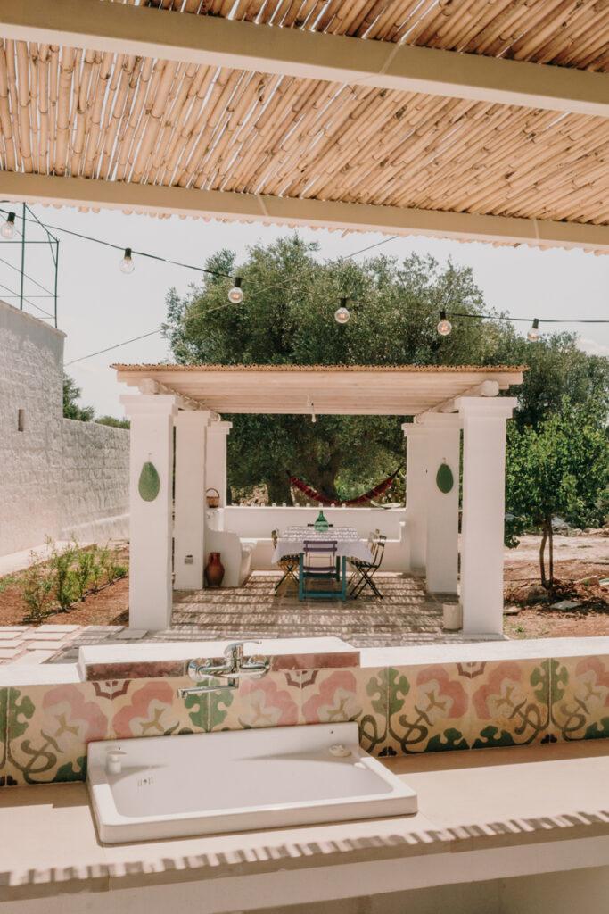 Salon extérieur sous une pergola. Au premier plan un plan de travail en béton et un évier en céramique blanche.