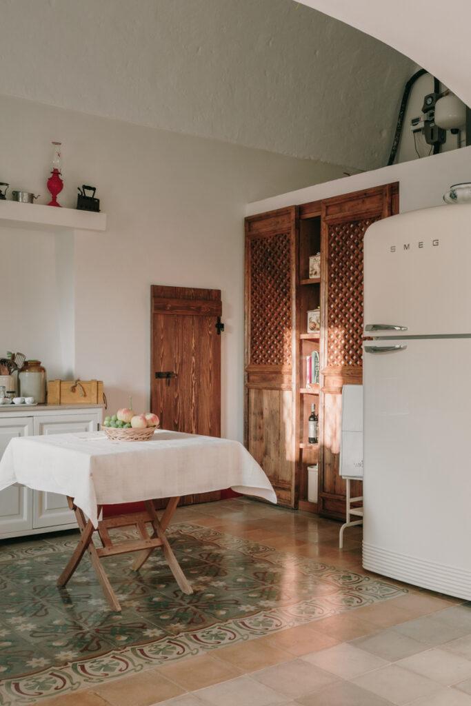 La cuisine intérieure, entre classicisme et modernité. Les mus sont en enduit chaux blancs, les meubles en bois et le frigo SMEG beige.