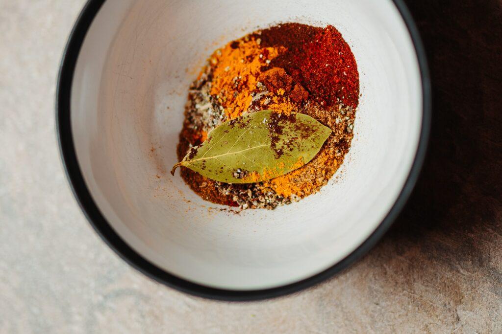 Cuisine zéro déchet : des épices et des aliments réduits en poudre dans un bol en émail blanc avec un bord noir sur une table en pierre.
